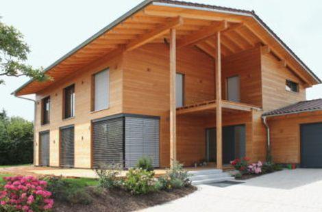 Großes Holzhaus mit Vordach und flachem Satteldach