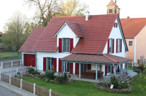 Holzhaus mit Satteldach und roten Fensterläden